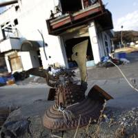 A rusting samurai warrior's helmet rests on broken concrete in in Otsuchi, Iwate Prefecture, an area devastated by the 2011 earthquake and tsunami. | AP