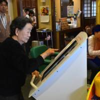 A resident of the nursing home Kaikaya in Yokohama  plays with a touchscreen game. | AFP-JIJI