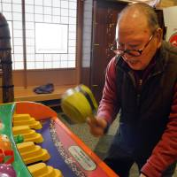88-year-old Saburo Sakamoto plays a game at Kaikaya Ltd., a nursing home run by an offshoot of Namco Bandai for the elderly in Yokohama. | AFP-JIJI