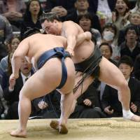 Sekiwake Goeido muscles out yokozuna Harumafuji on Friday, the 13th day of the Spring Grand Sumo Tournament. | KYODO