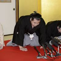 Kakuryu is flanked by stablemaster Izutsu (right) and his stablemaster's wife at Hoganji temple in Tennoji Ward, Osaka, on Wednesday upon being named yokozuna.