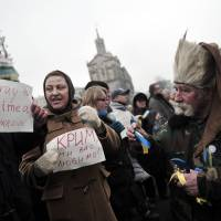People hold signs reading 'I pray for Crimea-Ukraine' during a rally Saturday in central Kiev, as pro-Russian forces tightened their grip on Crimea and the Kremlin vowed to help restore calm on the restive Ukrainian peninsula. | AFP-JIJI