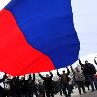 Pro-Russian protesters wave a giant Russian flag during a rally Saturday in Donetsk. More than 10,000 people protested in the eastern Ukrainian city of Donetsk, the stronghold of ousted president Viktor Yanukovych.  | AFP-JIJI
