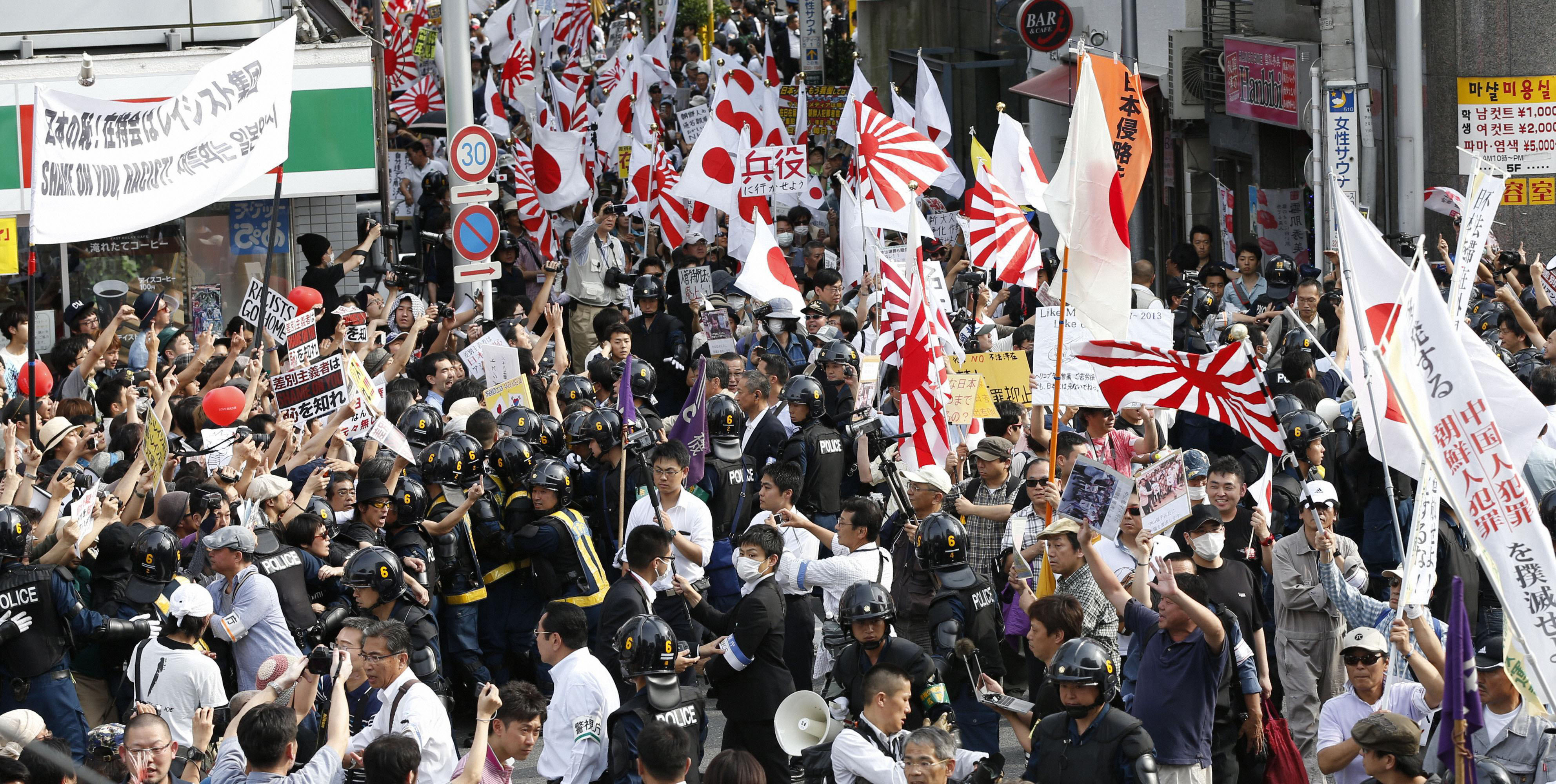 The far right that dare not speak its name: Police keep anti-Korean protesters away from anti-racist counterdemonstrators in Shinjuku, Tokyo, in June of last year. | KYODO