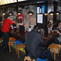 Fare stage: Diners at a Noodle Street eatery beneath the station.   STEPHEN CARR PHOTOS