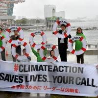 Members of environmental group Greenpeace display a banner and life preservers with the names of world leaders, during a protest over global warming held in front of the venue for a meeting of the Intergovernmental Panel on Climate Change in Yokohama on Sunday. | AFP-JIJI