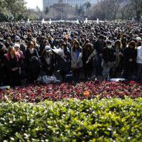 People at a rally in Tokyo on Tuesday observe a moment of silence at 2:46 p.m., the time the magnitude-9.0 quake struck off Tohoku in 2011. | REUTERS