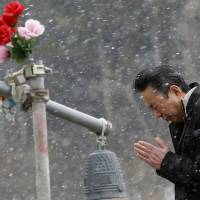 A man prays Tuesday in front of the main entrance of Okawa Elementary School in Ishinomaki, Miyagi Prefecture, where 74 of the 108 students went missing after the March 11, 2011, tsunami. | AP