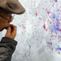 A visitor at the Center of the Tokyo Raids and War Damage in Koto Ward views a map Friday detailing how residents of the capital tried to flee U.S. air raids in 1945. | SATOKO KAWASAKI