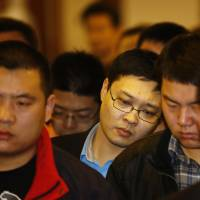 Relatives of Chinese passengers aboard Malaysia Airlines MH370 listen as a representative reads their complaints about the Malaysian government at the Lido Hotel in Beijing on Tuesday. | REUTERS