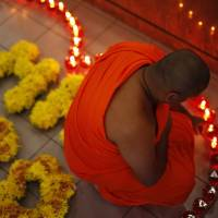 A monk lights candles for family members of passengers of Malaysia Airlines Flight MH370 at a special prayer meeting Saturday in Subang Jaya, outside Kuala Lumpur. | REUTERS