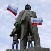 Pro-Russian protesters wave flags at the base of a statue of Vladimir Lenin in Donetsk, eastern Ukraine, on March 9. This industrial city of Porsches and poverty is torn between its Soviet past, a corrupt present and a future somewhere between Russia and the West. | REUTERS