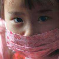 A girl wearing a face mask rides a school bus to the Emporium Kindergarten in the city of Koriyama, west of the crippled Fukushima No. 1 nuclear power station in Fukushima Prefecture, on Feb. 28. | REUTERS
