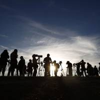 Television crews wait for an aircraft tasked with hunting for wreckage from Malaysia Airlines Flight MH370 to arrive at Pearce air base near Perth, Western Australia, on Friday. | REUTERS