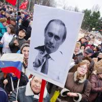 A protester holds a placard showing Russian President Vladimir Putin during a rally in support of Moscow in the Ukrainian city of Odessa on Sunday.   AFP-JIJI
