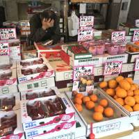 A worker at a fruit shop uses a calculator while awaiting customers at Tokyo's Tsukiji fish market on Friday. Household spending fell 2.5 percent in February from a year earlier, suggesting consumers are tightening belts ahead of Tuesday's consumption tax hike. | AP