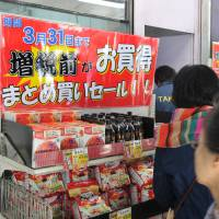 People shop at a Takeya discount store in Taito Ward, Tokyo, on Monday, the day before the consumption tax rises to 8 percent from 5 percent to slow Japan's ballooning debt.   YOSHIAKI MIURA