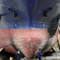 The Kyotoku Maru No. 18, a 330-ton vessel swept over 700 meters inland by the March 11 tsunami, towers above passers-by in Kesennuma, Miyagi Prefecture. The ship was removed last October.   AP
