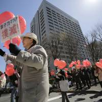 Anti-nuclear protesters hold balloons as they take part in a rally in front of the Ministry of Economy, Trade and Industry in central Tokyo on Tuesday. | AP