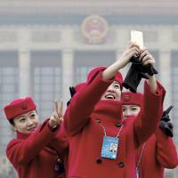 Stewardesses for the Chinese parliament's annual congress take a photo in Beijing on Monday. | AP