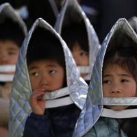Kindergartners take part in a quake evacuation drill in Chiyoda Ward, Tokyo, on Tuesday. | REUTERS