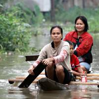 Residents paddle through a flooded village on the southern Philippine island of Mindanao on Jan. 13 following cataclysmic rainfall. | AFP-JIJI
