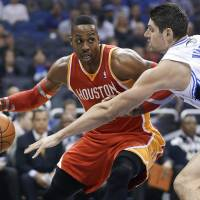 He's back: Rockets center Dwight Howard tries to get around the Magic's Nikola Vucevic during their game on Wednesday in Orlando. The Rockets won 101-89. | AP