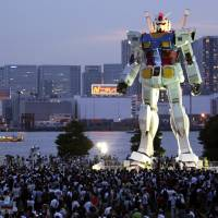 Silent defender: Giant robots, such as this 18-meter-high Gundam in Tokyo's Odaiba, are the subject of a government white paper. | AP