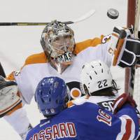 I got it: Flyers goalie Steve Mason and the Rangers' Derick Brassard watch the puck on Wednesday in New York. | AP