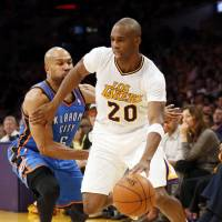Under the bright lights: Lakers guard Jodie Meeks drives around the Thunder's Derek Fisher on Sunday in Los Angeles. Meeks scored 42 points in the Lakers' 114-110 victory. | AP