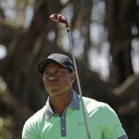 Poised for a Sunday run: Tiger Woods watches his tee shot on the fifth hole in the third round of the Cadillac Championship on Saturday. Woods carded a 66 and is three shots off the pace. | AP