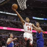 Streak continues: Chicago's D.J. Augustin goes up for a layup between Philadelphia's Michael Carter-Williams and Byron Mullens on Saturday night. The Bulls beat the 76ers 91-81. | AP