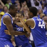 Big man on campus: Aaron Harrison (center) is hugged by teammates Julius Randle (left) and Dakari Jackson after his late 3-pointer against Michigan on Sunday in Indianapolis. | AP
