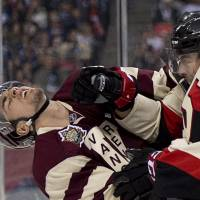 Get out of here: Senators defenseman Chris Phillips (right) punches Canucks winger Alex Burrows during their game on Sunday in Vancouver. The Senators rallied from two goals down to win 4-2.   AP