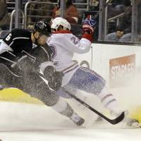 Board battle: Los Angeles' Jake Muzzin (left) vies for the puck with Montreal's Dale Weise on Monday night. | AP