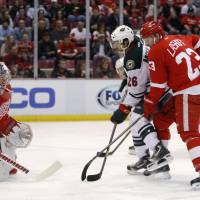 Running wild: Minnesota's Matt Moulson loses the puck in front of the Detroit net on Sunday. Moulson would later score the game-winner in overtime to lift the Wild over the Red Wings. | AP