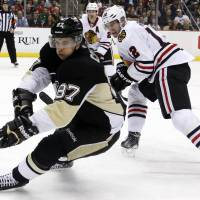 Just passing through: The Penguins' Sidney Crosby (left) skates past the Blackhawks' Peter Regin on Sunday in Pittsburgh. | AP