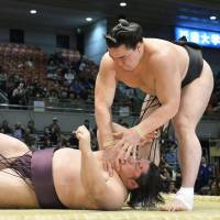Reality check: Harumafuji throws to Endo to the ground at the Spring Grand Sumo Tournament on Monday in Osaka. | KYODO