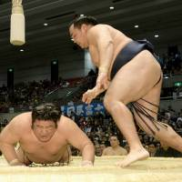 In contention: Kakuryu (right) remains one win off the pace after beating Tochiozan on Wednesday at the Spring Grand Sumo Tournament. | KYODO