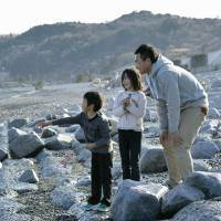 Subaru Niizuma, 6, accompanied by his sister Shizuku, 8, and father Atsushi, 40, throws a pink flower into the ocean in Iwaki, Fukushima Prefecture, on Sunday in honor of his grandmother, who died in the March 11 tsunami and was fond of pink flowers. | KYODO