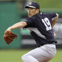 First start: New York's Masahiro Tanaka fires a pitch against Philadelphia in the second inning at spring training on Thursday. | AP