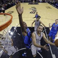 Back in style: Spurs guard Tony Parker goes in for a layup against the Mavericks' Samuel Dalembert during their game on Sunday in San Antonio. The Spurs defeated their in-state rivals from Dallas 112-106.   AP