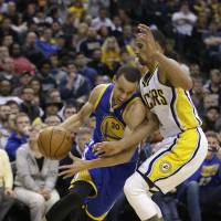 Bullrush: Golden State's Stephen Curry drives on Indiana's George Hill in the first half on Tuesday night. The Warriors won 98-96. | AP