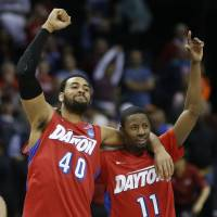 Flying high: Dayton's Devon Scott (40) and Scoochie Smith celebrate after their win over Stanford on Thursday.   AP