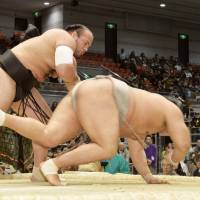 All-out effort: Osunaarashi (left) sends Takanoiwa tumbling to the raised ring during the Spring Grand Sumo Tournament on Friday in Osaka. | KYODO