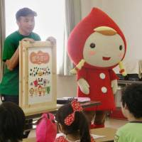 Yasuo Yamashita, head of the nonprofit group Kasumin in Kasugai, Aichi Prefecture, gives a talk on natural disasters to local children last August. | KYODO