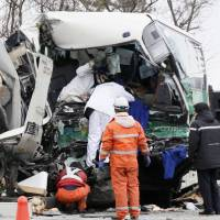 Bus hits parked trucks at rest area; two dead