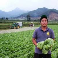 A young farmer displays some of his produce in the village of Kawakami, Nagano Prefecture, last September. | BLOOMBERG