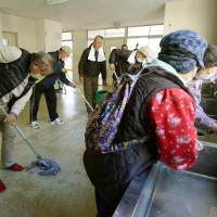 Evacuees from Futaba, Fukushima Prefecture, clean up on Friday the high school gym in Kasu, Saitama Prefecture, that had served as the last evacuation shelter for victims of the 2011 Fukushima No. 1 meltdown crisis.   KYODO