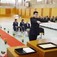 Mitsuhide Yoshida receives his graduation certificate during the commencement ceremony at Katsurao Junior High School in Miharu, Fukushima Prefecture, on Thursday. His fellow graduate, Daisuke Sato, is seated in the front row, third from the left. | KYODO